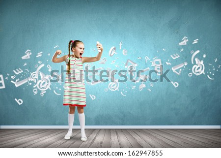 Image of little angry girl shouting in mobile phone - stock photo