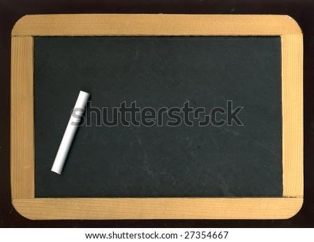 Image of little blackboard and chalk on black background - stock photo