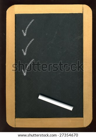 Image of little blackboard and chalk on black background