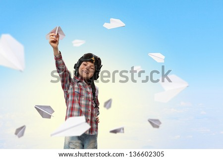Image of little boy in pilots helmet playing with paper airplane - stock photo