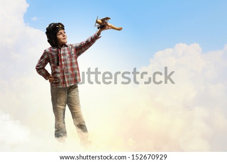 Image of little boy in pilots helmet playing with toy airplane against clouds background - stock photo