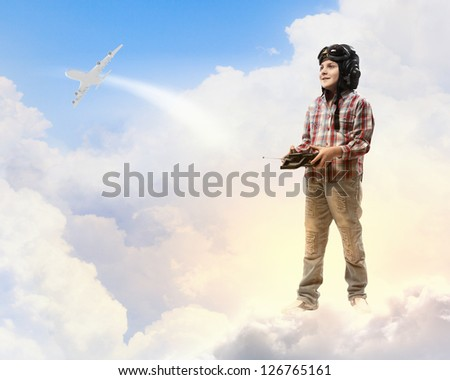 Image of little boy in pilots helmet playing with toy radiocontrolled airplane against clouds background - stock photo