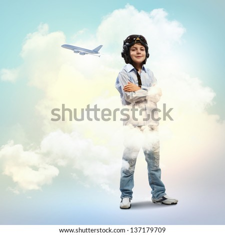 Image of little boy in pilots helmet with flying airplane in background - stock photo