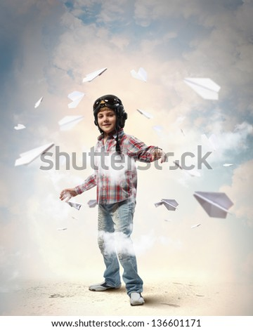 Image of little boy in pilots helmet with paper airplanes in background - stock photo