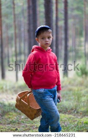 Image of Little boy walks forest path with wicker basket in autumn on mushrooming excursion - stock photo