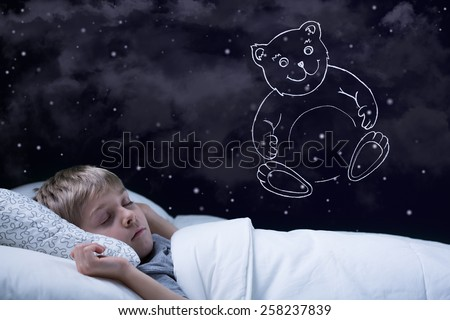 Image of little cute boy dreaming about his teddy bear - stock photo