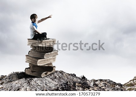Image of little cute boy sitting on pile of books - stock photo