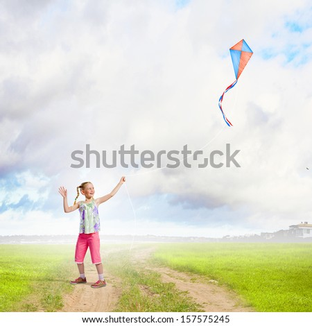 Image of little girl playing with kite at meadow - stock photo