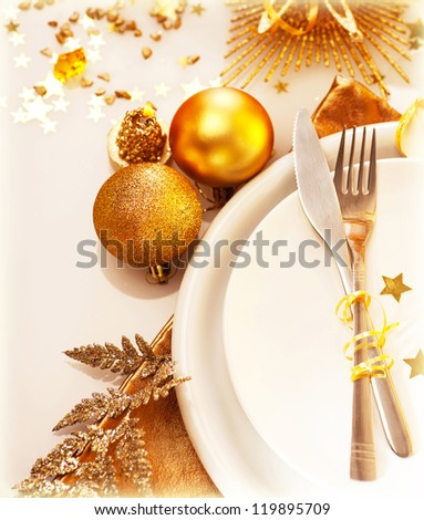 Image of luxury Christmas table setting, festive white dishware served with silver cutlery and decorated with beautiful golden candle and shiny bauble, New Year holiday, xmas celebration - stock photo