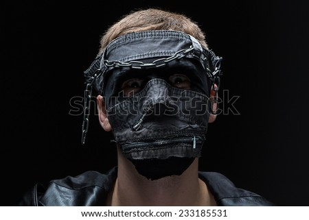 Image of madman in handmade mask on black background