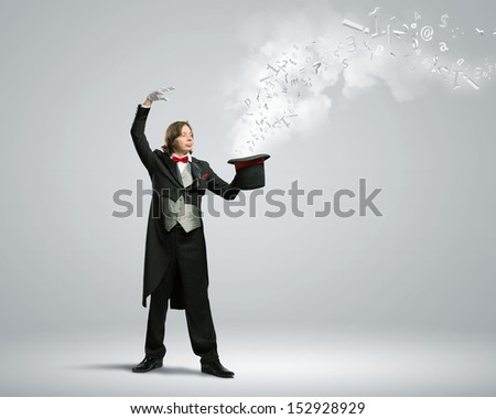 Image of magician holding hat with lights and fumes going out - stock photo