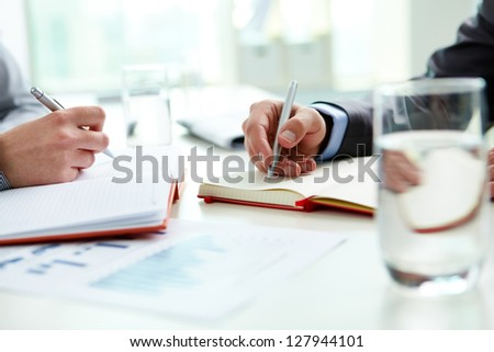 Image of male and female hands with pens over open notebooks at seminar - stock photo