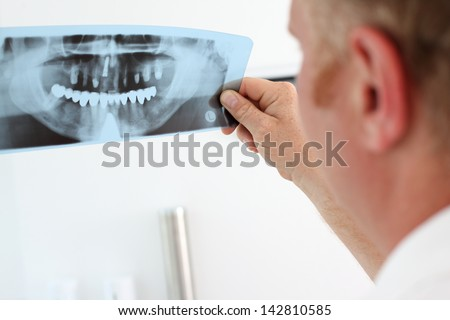 Image of male doctor holding and looking at dental x-ray - stock photo