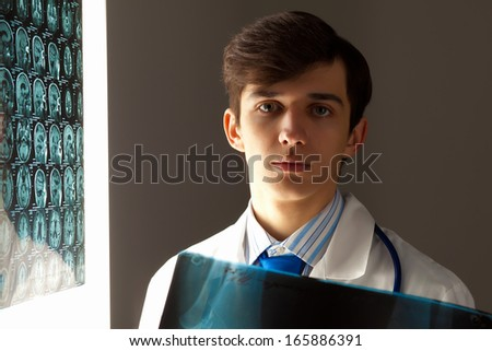 Image of male doctor holding x-ray results - stock photo