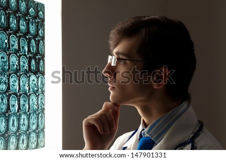 Image of male doctor looking at x-ray results - stock photo