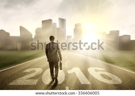 Image of male entrepreneur walking on the road with numbers 2016 while carrying suitcase