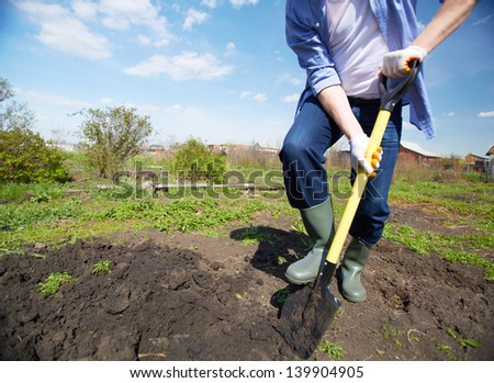 Image of male farmer in rubber boots didgging in the garden - stock photo