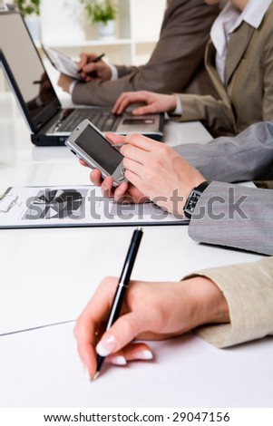 Image of male hand holding mobile palmtop device and working on it among partners - stock photo