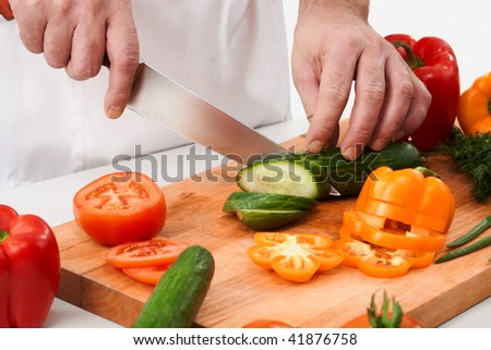 Image of male hand with knife cutting cucumbers on wooden board