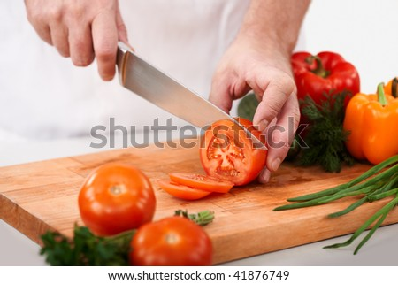 Image of male hand with knife cutting tomatoes on wooden chopping board - stock photo