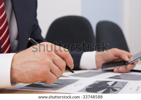 Image of male hand with pen over documents while planning work