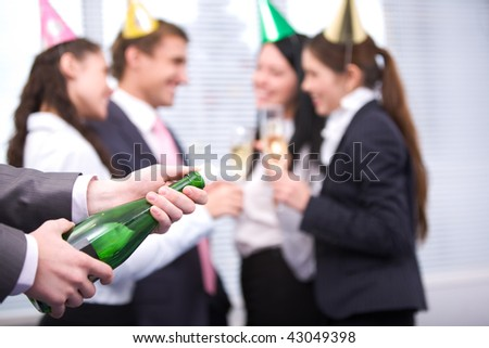 Image of male hands holding bottle of champagne and uncorking it - stock photo