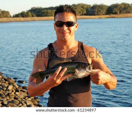 Image of male holding large mouth bass.  Image taken on an outdoor fishing trip in Northern California.