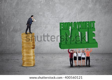 Image of male leader standing on the golden coins and shouting at his team to lift an employment rate text - stock photo