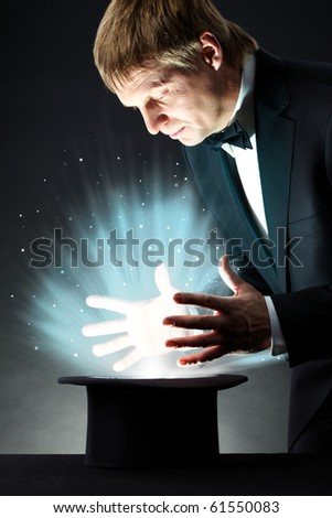Image of male magician looking into hat with magic light in darkness - stock photo