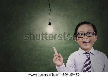Image of male student is getting an idea while pointing a bright light bulb in the classroom