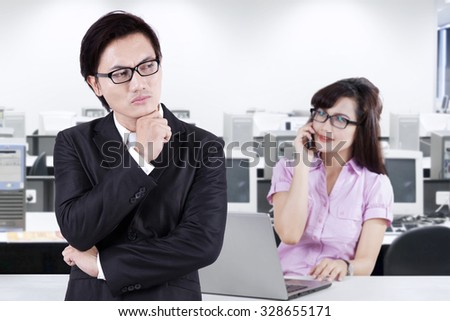 Image of male supervisor watching his employee talking on the phone while working with laptop in the office - stock photo