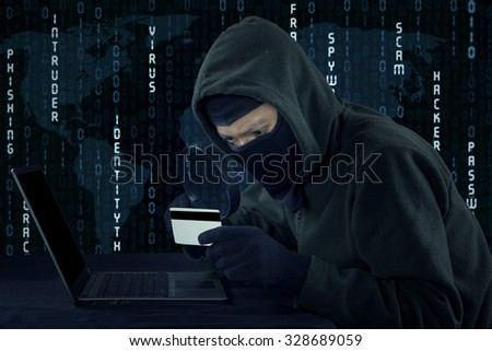 Image of male villain wearing mask and using laptop computer while holding credit card - stock photo