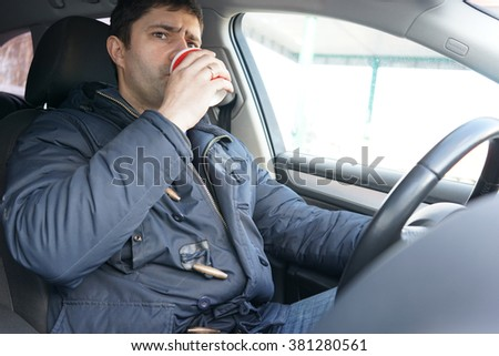 Image of Man drinking coffee in the car                                - stock photo