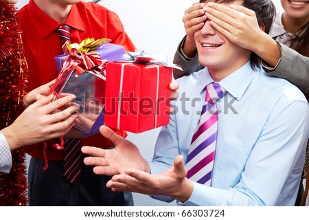 Image of man guessing what present he is going to receive from his colleagues - stock photo