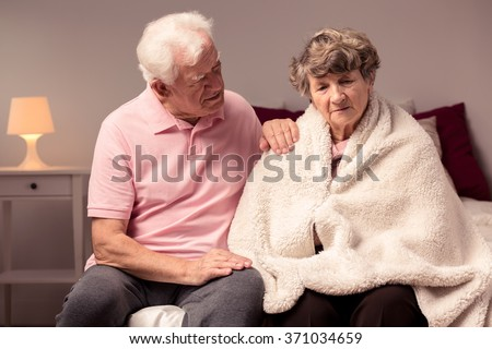 Image of man helping sad wife with health afflictions - stock photo