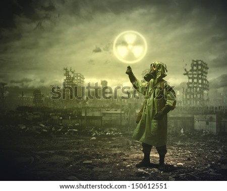 Image of man in gas mask and protective uniform touching radioactivity sign - stock photo