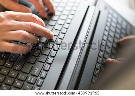 Image of man's hands typing on laptop keyboard. Selective focus. Close up