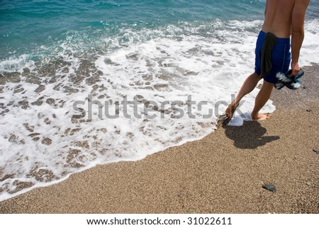 Image of man walking along seashore with surging wave by his legs - stock photo