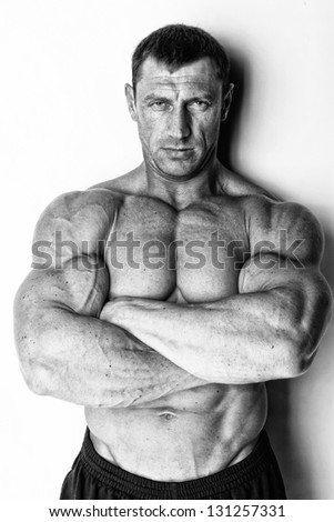 Image of man who gained a monster mass is posing with crossed hands on the white background - stock photo