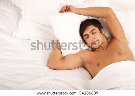 Image of man with one hand under pillow sleeping in bed - stock photo