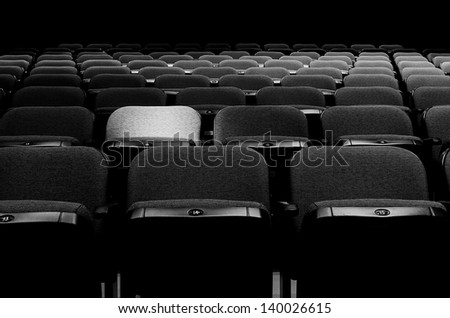 Image of many seats with spotlight on one of them - stock photo