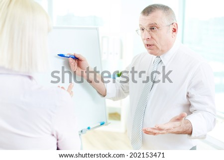Image of mature businessman teaching his partner on whiteboard at meeting - stock photo