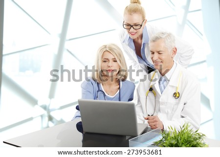 Image of medical staff consulting while sitting at desk in front of laptop at private clinic. Doctors and nurse analyzing the result of medical tests.  - stock photo
