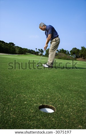 Image of mid-adult male putting golf ball with hole in foreground. - stock photo