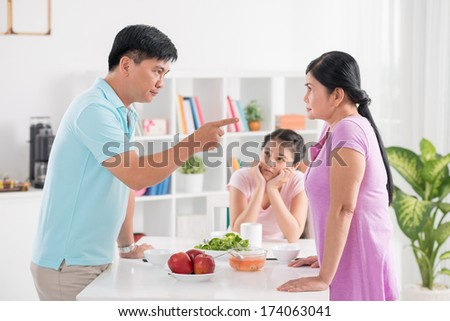 Image of middle-aged parents quarreling at breakfast within sight of their teenage daughter on the foreground  - stock photo