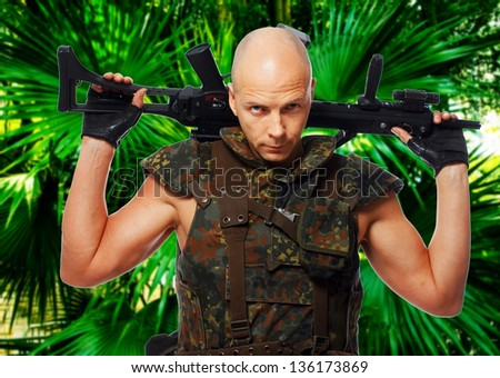 Image of military guy who is posing with his rifle - stock photo
