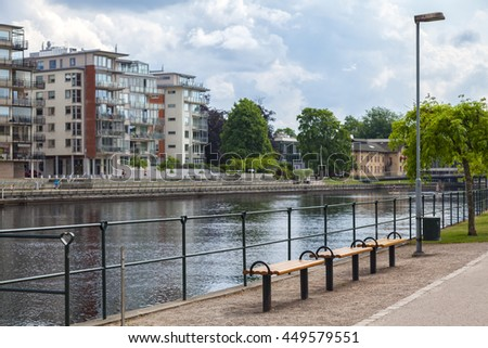 Image of modern buildings and benches by the river. Halmstad, Sweden.  - stock photo