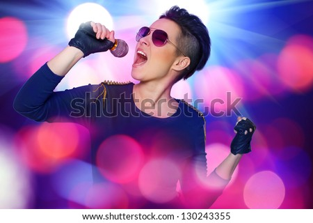 Image of modern rock singer who is screaming on the microphone during the photoset - stock photo