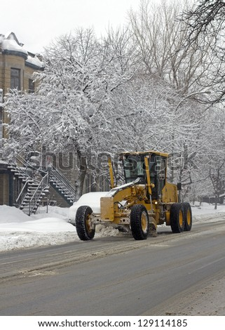 image of montreal in the winter with a snow cleaning vehicle - stock photo