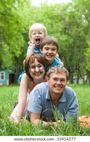 Image of mother, father and two brothers lying on the grass - stock photo